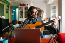 Middle Aged Ethnic Male Guitarist Tuning Acoustic Guitar Against Laptop And Photo Camera In House Room