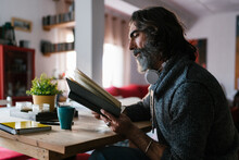 Side View Of Bearded Middle Aged Ethnic Male With Headset Reading Textbook At Home In Daylight