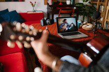 Side View Of Crop Male Musician Playing Classic Guitar While Watching Video Lesson On Netbook At Home