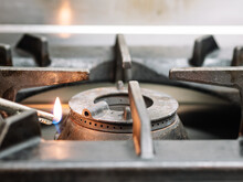 Crop Anonymous Chef Burning Gas Stove With Lighter Before Cooking In Kitchen At Restaurant
