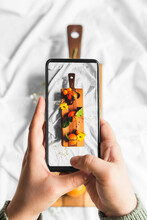 Top View Of Crop Unrecognizable Person Touching Screen Of Cellphone While Taking Photo Of Assorted Tropical Fruits On Cutting Board