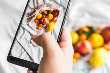 Overhead View Of Crop Unrecognizable Person Touching Screen On Mobile Phone While Taking Photo Of Fruits In Zero Waste Bag