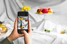 Crop Anonymous Person Taking Photo Of Fresh Kumquats And Blooming Flower Bouquet In Vase On Cellphone On White Background