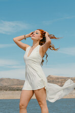 Young Gentle Female With Makeup And Closed Eyes In White Flying Dress Touching Red Hair Against River Under Blue Cloudy Sky
