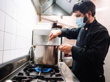 Side View Of Professional Male Cook In Mask Stirring Dish In Saucepan While Cooking On Stove In Kitchen Of Restaurant