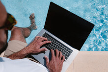 From Above Back View Of Male Freelancer In Sunglasses Sitting At Poolside And Browsing Netbook While Working Remotely On Project During Summer Vacation