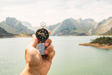 Closeup Of A Hand Holding A Compass In A Magnificent Landscape With River And Mountains