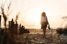 Back View Of Unrecognizable Female In Summer Clothes Walking Towards Sea Along Sandy Beach On Background Of Sundown Sky