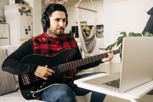 Adult Male Musician In Headphones Playing Bass Guitar Against Netbook On Sofa In Living Room