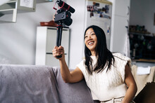 Smiling Ethnic Female Vlogger Recording Video On Photo Camera While Sitting On Couch In Living Room