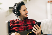 Adult Bearded Male Musician With Bass Guitar In Headphones Text Messaging On Cellphone In Living Room