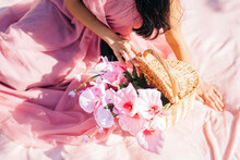From Above Crop Peaceful Asian Woman In Pink Dress Sitting On Plaid With Blooming Flowers In Wicker Basket In Lush Garden And Looking Down
