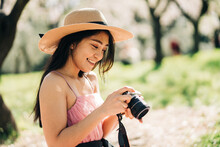 Side View Of Focused Ethnic Female In Straw Hat Taking Photo On Camera In Garden With Blooming Trees