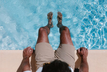 Top View Of Unrecognizable Male Freelancer Sitting At Poolside With Legs In Water During Telework In Summer