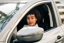 Side View Of Serious African American Female Driver In Fashionable Outfit Driving Modern Automobile On The Street Looking At Camera
