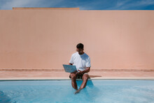 Male Freelancer In Sunglasses Sitting At Poolside And Browsing Netbook While Working Remotely On Project During Summer Vacation
