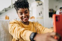 Charming African American Female With Curly Hair Taking Self Portrait On Smartphone While Sitting On Sofa At Home