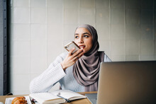 Content Ethnic Female Freelancer In Hijab Recording Audio Message On Smartphone While Sitting At Table In Cafe And Working Remotely