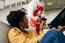 Low Angle Of Multiracial Couple Clicking Glasses With Red Wine While Enjoying Weekend At Home