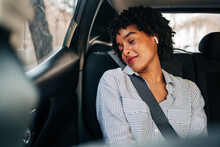 Carefree Young African American Female With TWS Earbuds Listening To Music With Eyes Closed Resting In Modern Automobile