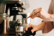 Unrecognizable Female With Spoon Pouring Ground Coffee Into Portafilter While Standing At Kitchen Counter With Jar Of Coffee And Coffee Machine On Blurred Background
