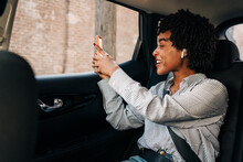 Side View Of Cheerful African American Female Smiling And Talking In Video Chat In Mobile Phone In Modern Automobile