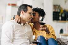 Content Multiracial Couple Chilling On Sofa At Home With Red Wine In Glasses While Enjoying Weekend At Home And Kissing