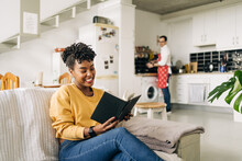 Delighted African American Female Reading Interesting Book On Sofa On Background Of Man Cooking In Kitchen
