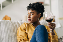Content African American Female Sitting On Sofa With Glass Of Red Wine And Enjoying Weekend At Home While Looking Away