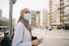 Side View Of Ethnic Female Wearing Headscarf And Protective Mask Standing On Street In City On Sunny Day And Looking Away