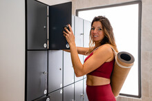 Side View Of Calm Happy Sportswoman In Activewear Standing With Rolled Yoga Mat And Closing Locker In Gym Before Workout In Daytime Looking At Camera
