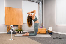 Side View Of Unrecognizable Barefooted Female In Activewear Doing Kneeling With Prayer Hands Yoga Pose On Mat Near Laptop And Smartphone On Tripod While Shooting Tutorial Video