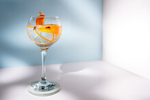 Transparent Glass Of Highball Cocktail Decorated With Citrus Fruit Zest And Clove Against Shadows In Sunlight