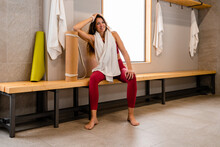 Tired Glad Sportswoman In Sportswear Sitting With Towel On Shoulders On Wooden Bench In Gym Locker Room After Training