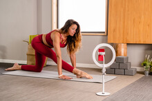 Tripod With Smartphone Placed On Floor Near Graceful Female Instructor In Sportswear Stretching Legs In Half Splits Asana During Filming Yoga Course