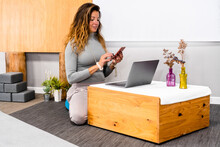 Content Young Female With Long Hair In Casual Clothes Messaging On Smartphone While Working Remotely On Laptop Sitting On Floor At Small Wooden Table In Minimalist Apartment