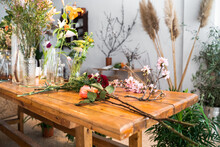 Thorny Roses With Carnation And Blooming Sakura Tree Twigs Placed On Wooden Table In Light Florist Shop With Assorted Colorful Flowers On Sunny Day
