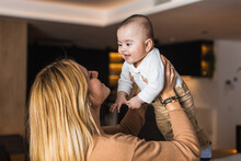 Side View Of Delighted Mother Tossing Adorable Smiling Baby While Having Fun Together At Home