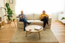High Angle Of Mature Man Using Smartphone And Middle Aged Woman Browsing Tablet While Sitting On Couch In Living Room At Home