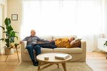 Delighted Middle Aged Couple Relaxing On Comfortable Couch In Cozy Living Room While Holding Hands And Looking At Each Other