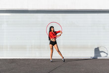 Young Tattooed Woman In Activewear Twirling Hula Hoop While Dancing Against Brick Walls With Shadows