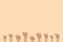 Minimalistic Composition Of Wooden Hands Demonstrating Fists As Symbol Of Protest Placed Against Beige Background