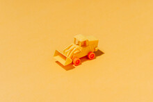 High Angle Collection Of Similar Tractor Toys Symmetrical Arranged On Yellow Surface As Abstract Background