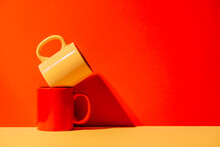Creative Colorful Mugs On Yellow And Red Background In Studio