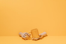 Creative Ornamental Wooden Hand Holding Colorful Mug On Yellow Background In Studio
