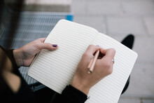 High Angle Of Crop Unrecognizable Female Entrepreneur Sitting On Bench In City And Writing Business Plan In Notebook