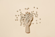 Top View Of Wooden Hand With Pile Of Alphabet Letters On Cubes Scattered On Beige Background In Studio