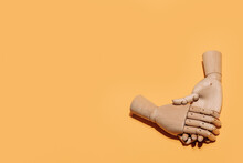 Top View Of Wooden Hands Demonstrating Handshake As Sign Of Agreement Placed On Yellow Background