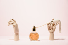 Stylish Transparent Bottle Of Perfume Placed Between Wooden Hands Placed On Pink Background In Light Studio