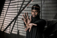 Determined African American Male Showing Gesture At Camera While Standing In Underground Parking In City